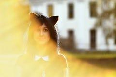 Gullig flicka med leksakkattöron på huvudet i solstråleljus Royaltyfri Fotografi
