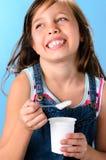 Gullig flicka med probiotic rik yoghurt royaltyfri fotografi