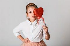 Gullig flicka med röd hjärta på pinnar Fira Sankt dag för valentin` s arkivbild