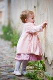 gullig flicka nära den gammala små plattform väggen Arkivbild