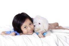 Gullig flicka och maltese hund på säng Royaltyfri Bild