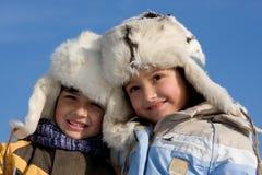 Gullig flicka och pojke i päls-locket Royaltyfria Foton