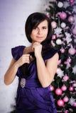 Gullig flicka på bakgrunden av julgranen Royaltyfria Bilder