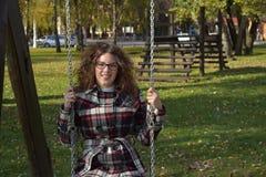 Gullig flicka på en gunga i parkera Royaltyfria Bilder