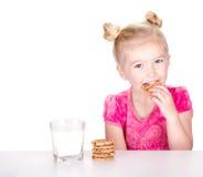 Gullig flicka som äter en choklad kaka Arkivbild