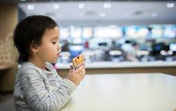 Gullig flicka som äter en hamburgare i snabbmatet Arkivbilder