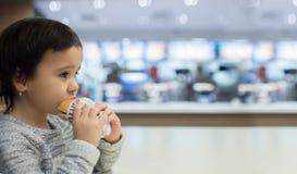 Gullig flicka som äter en hamburgare i snabbmatet Royaltyfria Bilder