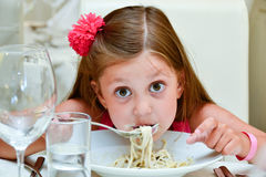 Gullig flicka som äter pasta Arkivbild