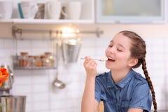 Gullig flicka som äter smaklig yoghurt royaltyfri foto