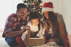 Gullig flicka som öppnar en gåva på en julmorgon med hennes familj fotografering för bildbyråer