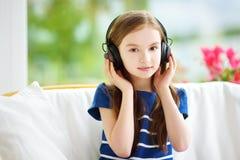 Gullig flicka som bär enorm trådlös hörlurar Nätt barn som lyssnar till musiken Skolflicka som har gyckel som lyssnar till sånger Arkivfoton