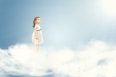 Gullig flicka som barfota står på moln Arkivfoto
