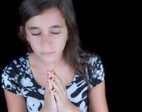 Gullig flicka som ber med hennes stängda ögon Fotografering för Bildbyråer