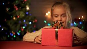 Gullig flicka som beundrar den röda gåvaasken med den stora guld- pilbågen, barndrömmar, xmas-magi arkivfoton