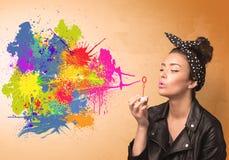 Gullig flicka som blåser färgrika färgstänkgrafitti Arkivbilder
