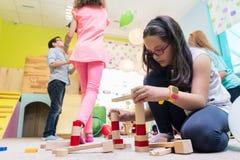 Gullig flicka som bygger en struktur i jämvikt under rast på dagiset arkivfoton