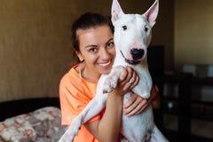 Gullig flicka som daltar hennes bull terrier Härlig flicka som har gyckel med hennes bull terrier och tycker sig om Flicka och he Royaltyfri Fotografi