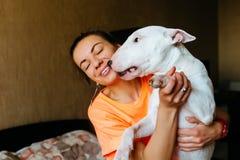Gullig flicka som daltar hennes bull terrier Härlig flicka som har gyckel med hennes bull terrier och tycker sig om Flicka och he Royaltyfri Bild