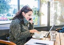 Gullig flicka som dricker cappuccino, talar på telefonen och skriver på en minnestavla Arkivbild