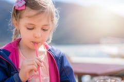 Gullig flicka som dricker fruktsaft i sommar arkivbild