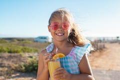 Gullig flicka som dricker orange fruktsaft royaltyfria bilder