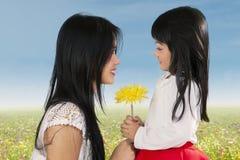 Gullig flicka som ger blomman till hennes mamma Royaltyfri Foto