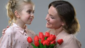 Gullig flicka som ger blommor till den ?lskade modern, ?verraskningen f?r f?delsedag eller mars 8 lager videofilmer