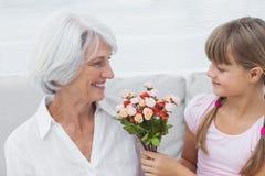 Gullig flicka som ger en grupp av blommor till hennes farmor Arkivfoton