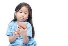 Gullig flicka som håller ögonen på på mobiltelefonen Arkivfoto