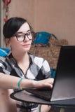Gullig flicka som hemma arbetar på bärbara datorn, brunett i svarta exponeringsglas Arkivfoton