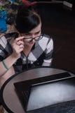 Gullig flicka som hemma arbetar på bärbara datorn, brunett i svarta exponeringsglas Arkivbilder