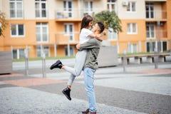 Gullig flicka som hoppar för att man soligt, sommardag Förälskat krama för stilfulla par och kyssa i stadsgata Förhållande mest l Royaltyfria Bilder