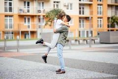 Gullig flicka som hoppar för att man soligt, sommardag Förälskat krama för stilfulla par och kyssa i stadsgata Förhållande mest l Fotografering för Bildbyråer
