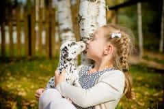 Gullig flicka som kysser hennes valp, vovve på den wood staketbakgrunden Lycklig flicka med en hund som slickar hennes framsida v royaltyfria bilder
