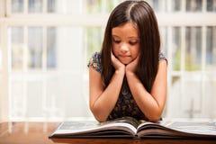 Gullig flicka som läser en sagobok Fotografering för Bildbyråer