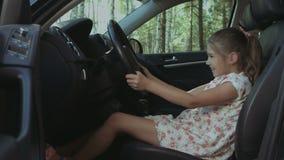 Gullig flicka som låtsar för att köra förälderbilen arkivfilmer