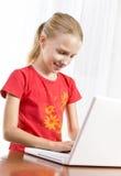 Gullig flicka som leker på bärbar dator royaltyfri fotografi