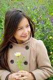 Gullig flicka som ler den hållande blomman Royaltyfri Fotografi