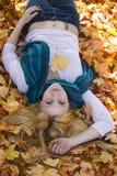 Gullig flicka som ligger i fallleavesna arkivbild