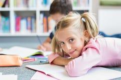 Gullig flicka som ligger på att studera för golv arkivbild