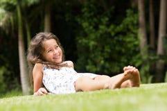 Gullig flicka som ligger på gräs arkivfoton