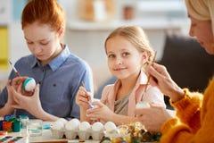 Gullig flicka som målar ägg för påsk royaltyfri fotografi