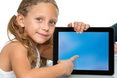 Gullig flicka som pekar på den blanka tabletskärmen. Royaltyfri Foto