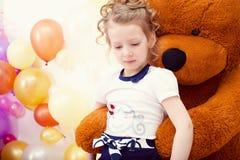 Gullig flicka som poserar i omfamning med den stora nallebjörnen Royaltyfri Fotografi