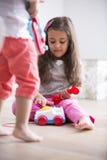 Gullig flicka som ringer leksaktelefonen, medan spela med den hemmastadda systern Royaltyfri Bild