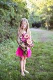 Gullig flicka som rymmer en grupp av blommor Royaltyfria Foton