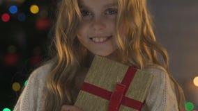 Gullig flicka som rymmer julklapp som ler på kameran, lycklig barndom, closeup lager videofilmer