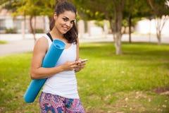 Gullig flicka som smsar för yoga Royaltyfri Bild
