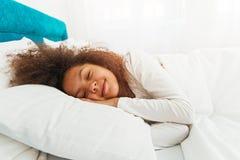 Gullig flicka som sover i sängen royaltyfri foto