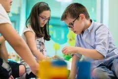 Gullig flicka som spelar bredvid hennes kollega i klassrumet arkivbild